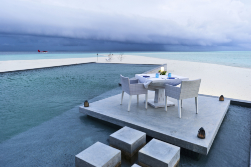 dining table on the deck of outdoor swimming pool in beach resort